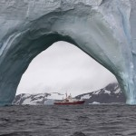 RRS James Clark Ross through an iceberg arch